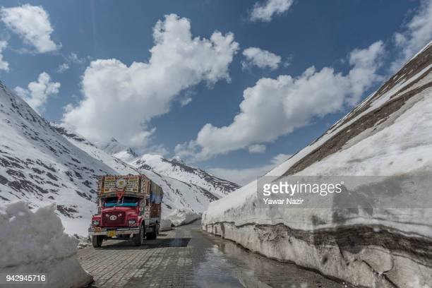 A vehicle passes through the snowcleared SrinagarLeh highway on April 6 2018 in Zojila 108 km east of Srinagar the summer capital of Indian...