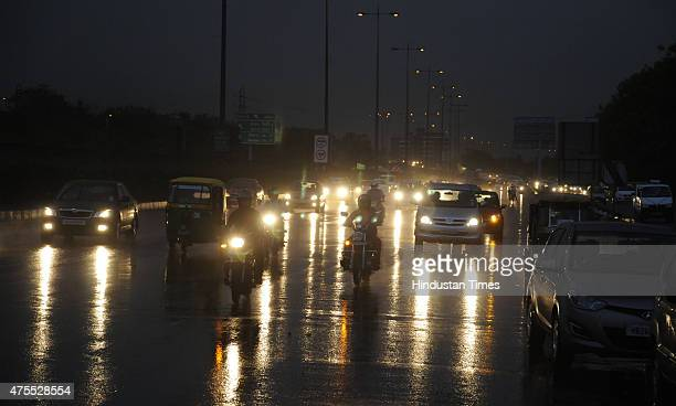 Vehicle plying in a sudden thunder storm and rain at DelhiGurgaon expressway on June 1 2015 in Gurgaon India Overcast skies followed by scattered...