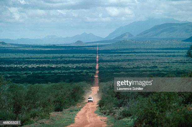 A vehicle rides along a dusty road that cuts across the wilderness Kenya 1977