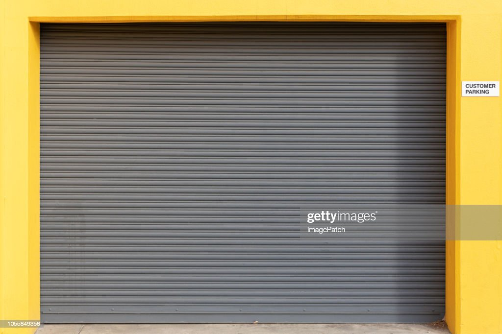 Vehicle roller door set in bright yellow wall : Stock Photo