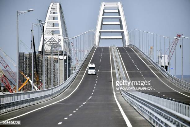 A vehicle runs down the 19 km roadandrail Crimean Bridge passing over the Kerch Strait and linking southern Russia to the Crimean peninsula on May 15...