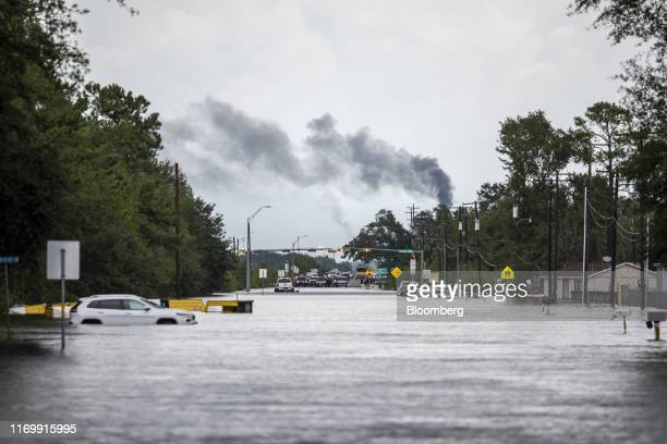 A vehicle sits submerged in a flooded street while smoke rises from a refinery following Tropical Storm Imelda in Fannett Texas US on Friday Sept 20...