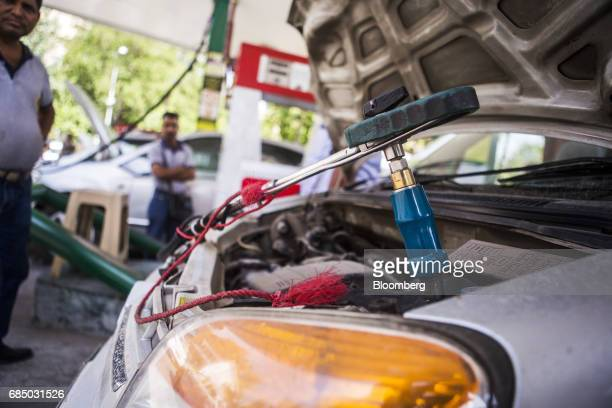 A vehicle sits with a fuel nozzle connected to it while being refueled with compressed natural gas at an Indraprastha Gas Ltd gas station in New...