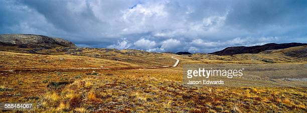 A vehicle track winds across a remote tundra hillside.