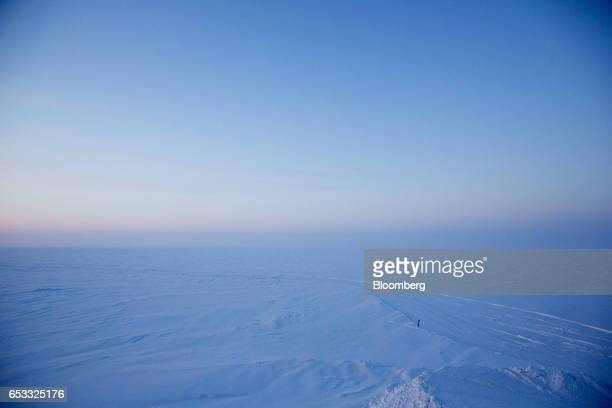 Vehicle tracks cover an ice road on the frozen Beaufort Sea near the Caelus Energy LLC Oooguruk Development Project in Harrison Bay Alaska US on...