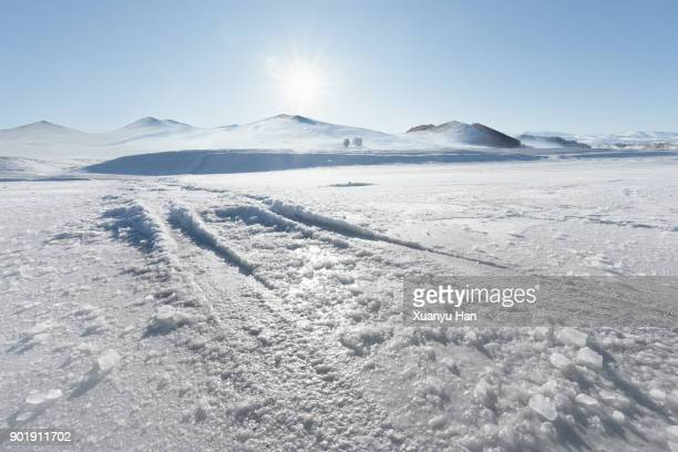 Vehicle tracks through thick layer of ice, with blue sky and sun above.
