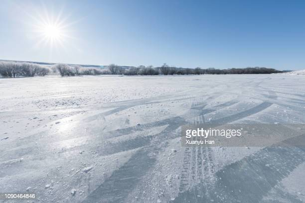 vehicle tracks through thick layer of ice, with blue sky - 道 ストックフォトと画像