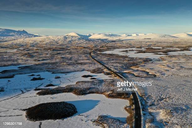 Vehicle travel on the A82 past a frozen over Lochan na Achlaise as freezing temperatures continue on January 8, 2021 in Glen Coe, Scotland. The Met...