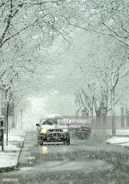 A vehicle travels up a city street during heavy snowfall April 24 2005 in Bowling Green Ohio The unusual spring snowstorm hit most of northern Ohio...