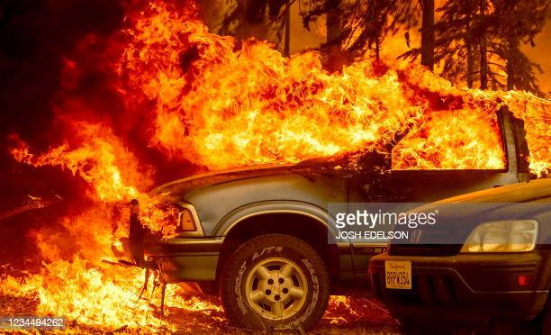 Vehicles and a home are engulfed in flames as the Dixie fire rages on in Greenville, California on August 5, 2021. - Evacuation orders were widened...