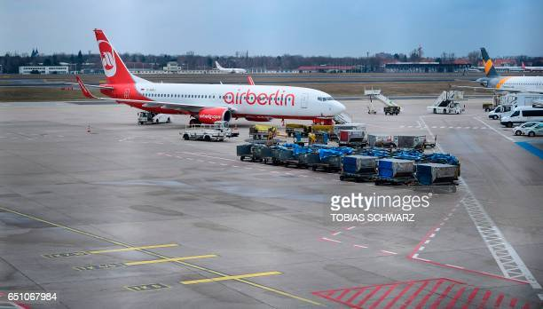 Vehicles and a plane of German airline Air Berlin are parked at the tarmac during a wage strike of ground staff at Berlin's Tegel airport on March 10...