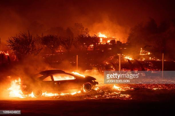 TOPSHOT Vehicles and homes burn as the Camp fire tears through Paradise California on November 8 2018 More than 18000 acres have been scorched in a...
