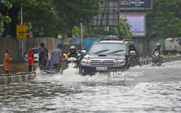 Vehicles and people wade through waterlogged street at SV RoadKhar on July 9 2018 in Mumbai India Indias financial capital and its surrounding...