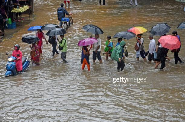 Vehicles and people wade through waterlogged street near WEH metro station at Andhri Kurla Road on July 11 2018 in Mumbai India Heavy rains made a...