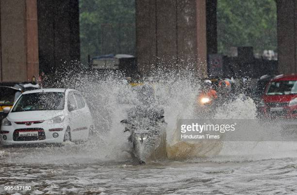 Vehicles and people wade through waterlogged street on WEH at Jogeshwari on July 9 2018 in Mumbai India Indias financial capital and its surrounding...