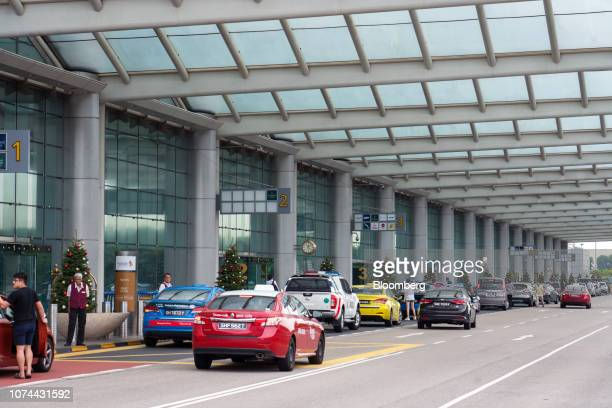 Vehicles and taxis sit parked at a passenger dropoff area at Terminal 2 of Changi Airport in Singapore on Thursday Dec 13 2018...