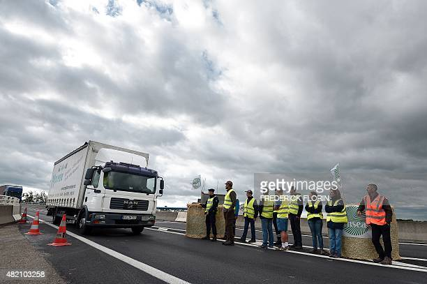 Vehicles are blocked by farmers protesting on a bridge between France and Germany in Strasbourg eastern France on July 27 2015 The French government...