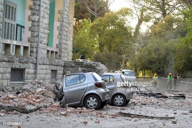 Vehicles are crushes as emergency services workers clear the ruins of a collapsed building roof in Tirana on September 21 after two earthquakes over...