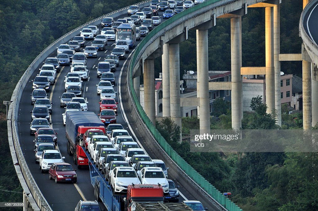Vehicles are driven along a freeway on the fifth day of the National Day holiday on October 5, 2014 in Suichuan, China. China's golden-week National Day holiday is expected to bring a tourism peak throughout the country.