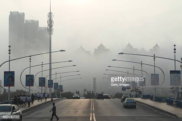 Vehicles are driven along a road as heavy fog engulfs the city on June 10 2014 in Dalian China Dalian meteorological bureau has issued an orange...