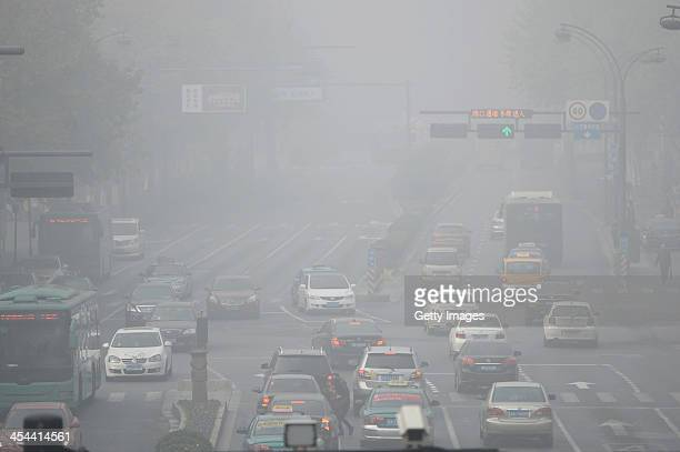 Vehicles are driven along a road on December 8 2013 in Hangzhou China Heavy smog has been lingering in northern and eastern parts of China since last...