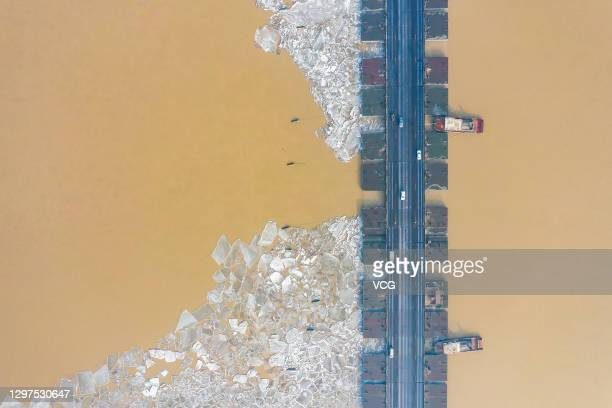 Vehicles are driven on a bridge as ice floes appear on the Yellow River on January 20, 2021 in Binzhou, Shandong Province of China.