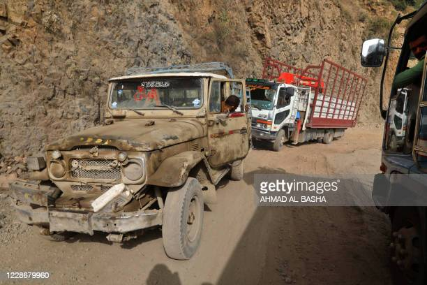 Vehicles are pictured at a heavily damaged road, the only travel route between Yemen's cities of Taez and Aden, on September 23, 2020. - Yemen has...