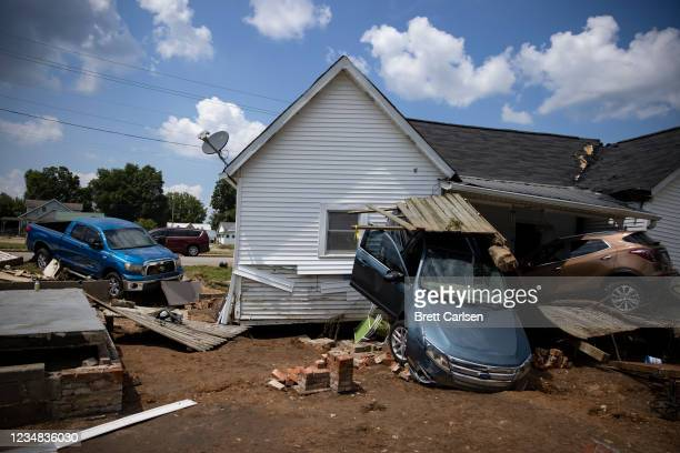 Vehicles are piled up next to a house destroyed by flooding on August 23, 2021 in Waverly, Tennessee. Heavy rains on Sunday caused flash flooding in...
