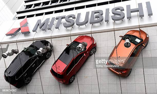 Vehicles are reflected in the mirror of the headquarters of Japan's auto maker Mitsubishi Motors in Tokyo on July 27 2016 The auto maker will...