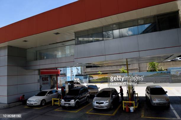 Vehicles are seen at a gas station in Caracas where people are queueing for petrol on August 17 2018 for the uncertainty about the price and...