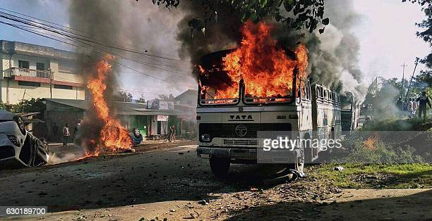 Vehicles are seen burning after being set alight by protesters in Imphal the capital of Indias northeastern state of Manipur on December 18 2016 The...