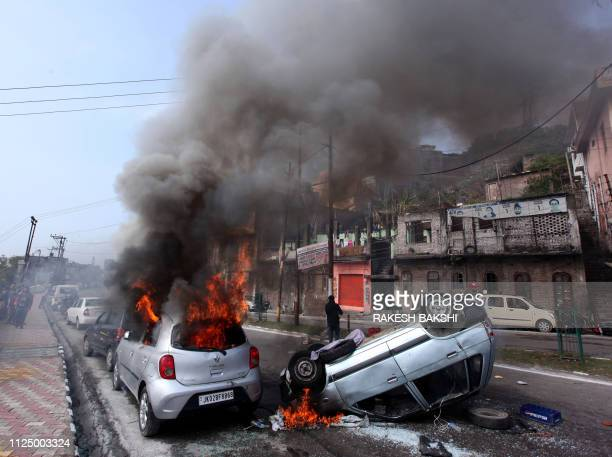 Vehicles are seen burning along a road during a protest in Jammu on February 15 the day after an attack on a paramilitary Central Reserve Police...