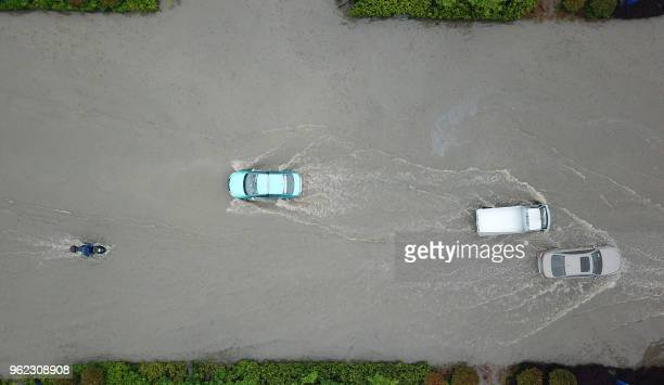Vehicles are seen on a waterlogged street after heavy rainfall in Yangzhou in China's eastern Jiangsu province on May 25 2018 Heavy rain swept parts...