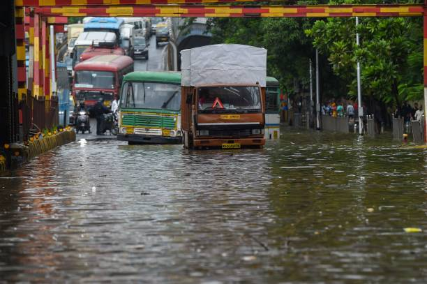 Vehicles are seen stranded on a waterlogged road after a heavy monsoon rainfall in Mumbai on July 16, 2021.