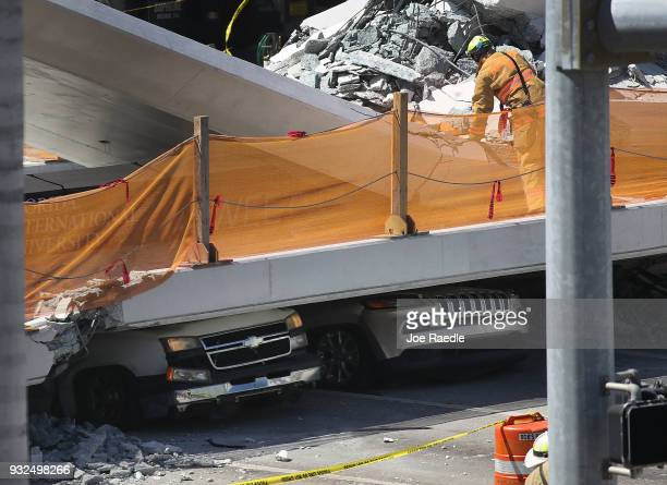 Vehicles are seen trapped under the collapsed pedestrian bridge that was newly built over southwest 8th street allowing people to bypass the busy...