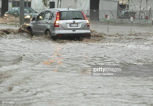 Vehicles attempt to drive through a flooded section of Batman Avenue as massive storms hit Melbourne city on March 6, 2010 in Melbourne, Australia. A...
