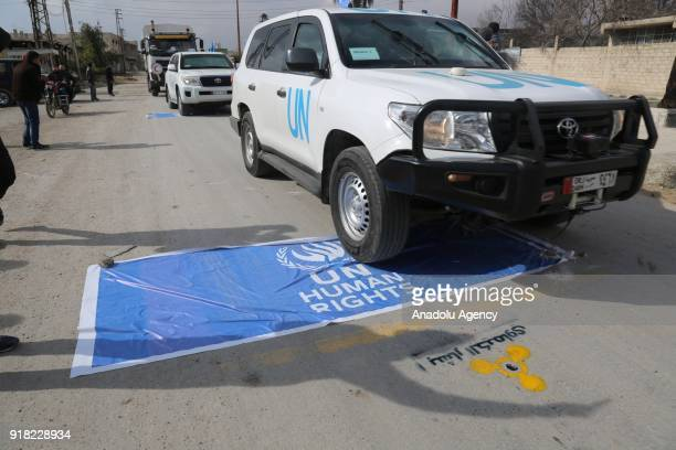 Vehicles belonging to United Nations drive over a banner reading 'UN Human Rights as Syrians wearing gas masks hold banners during a protest against...