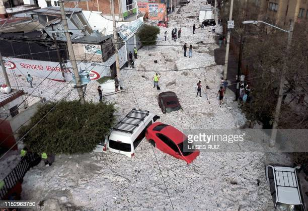Vehicles buried in hail are seen in the streets in the eastern area of Guadalajara, Jalisco state, Mexico, on June 30, 2019. - The accumulation of...