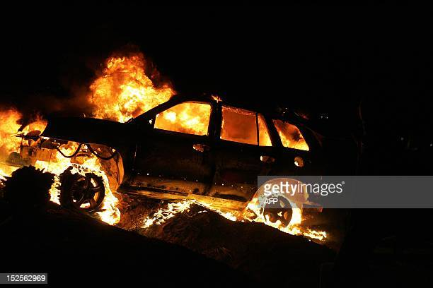 Vehicles burn after armed Libyan demonstrators stormed the headquarters of the Raf Allah alSahati Brigade a local militia located at a farm in the...