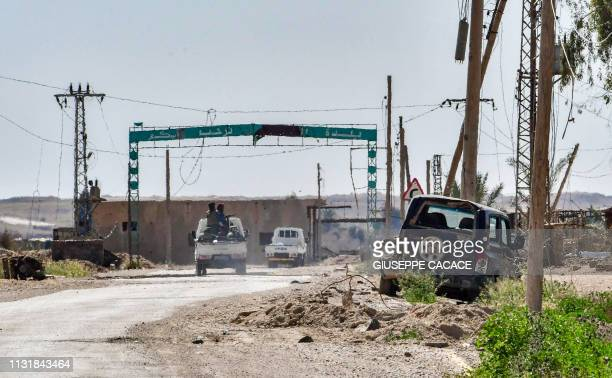 Vehicles carrying fighters of the USbacked Kurdishled Syrian Democratic Forces pass under an arch at the entrance of the village of Baghouz in the...