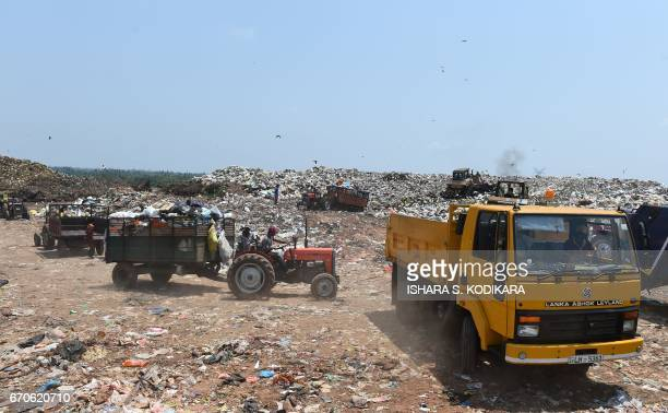 Vehicles carrying garbage reach a new dump at Karadiyana a suburb of Colombo on April 20 after the city's main landfill closed after a garbage...