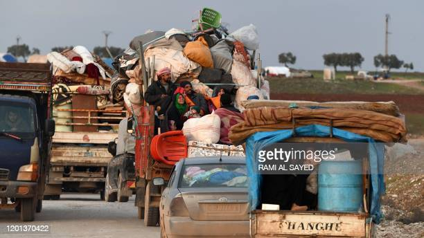 Vehicles carrying internally-displaced persons and their belongings drive past the IDP camp by Dayr Ballut near the Turkish border in the west of the...