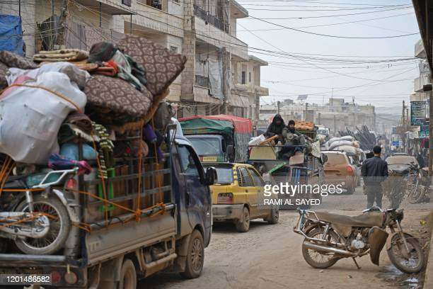 Vehicles carrying internally-displaced persons and their belongings drive through the Syrian town of Atme near the Turkish border towards the city of...