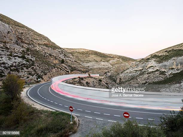 Vehicles circulating along a road with curves to the dusk, with the flushed lights