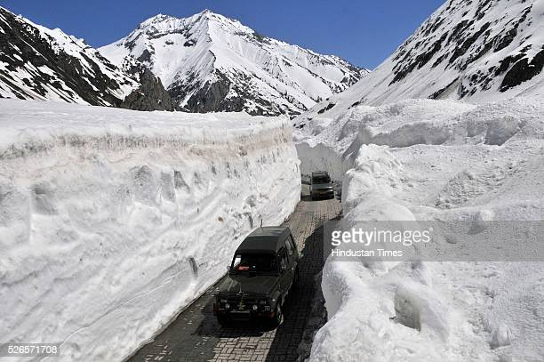 Vehicles cross through a snow bound Zojila pass 108 kilometers east of Srinagar on April 30 2016 in Srinagar India The SrinagarLeh road link was...