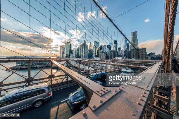 Vehicles crossing Brooklyn Bridge in sunlight with winter sky