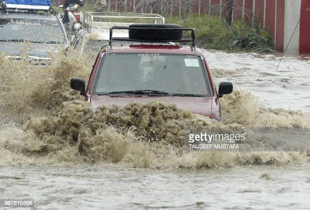 Vehicles drive along a flooded road after a heavy rainfall in Srinagar on June 30 2018 Authorities issued a flood alert in central Kashmir for low...