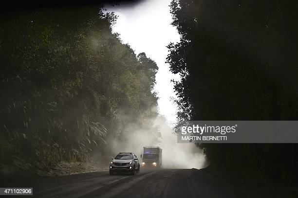 Vehicles drive along a road covered with ashes from the Calbuco volcano in La Ensenada, southern Chile, on April 25, 2015. Authorities ordered the...