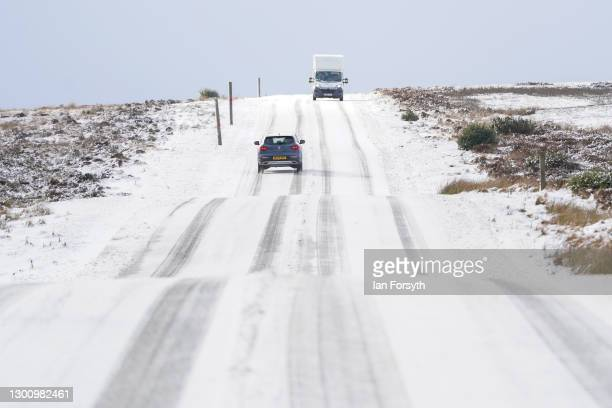 Vehicles drive along a snow covered road on the North Yorkshire Moors on February 08, 2021 in Castleton, United Kingdom. Heavy snow in Scotland and...