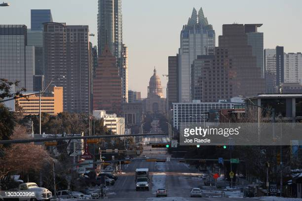 Vehicles drive along Congress Avenue that leads to the Texas Capitol building on February 19, 2021 in Austin, Texas. Winter storm Uri brought...